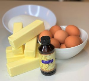 sticks of butter, brown eggs, sugar and vanilla extract bottle