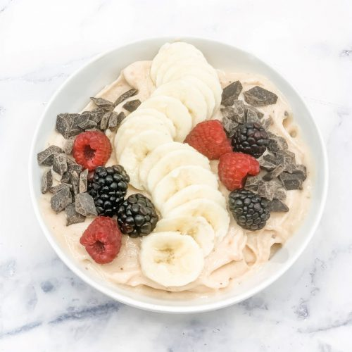 Smoothie bowl with bananas, berries and chocolate pieces