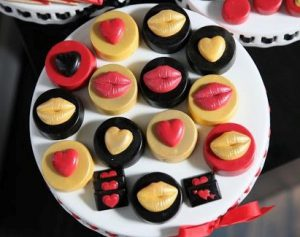Chocolate dipped oreos with chocolate molds of lips and hearts on top