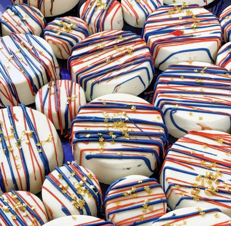 Oreo cookies covered in white chocolate with red and blue stripes and gold specks
