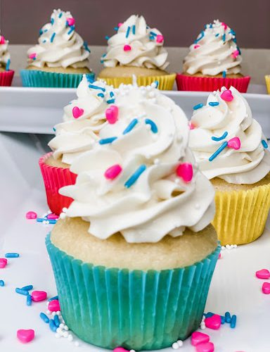 vanilla cupcakes with vanilla frosting and colorful sprinkles